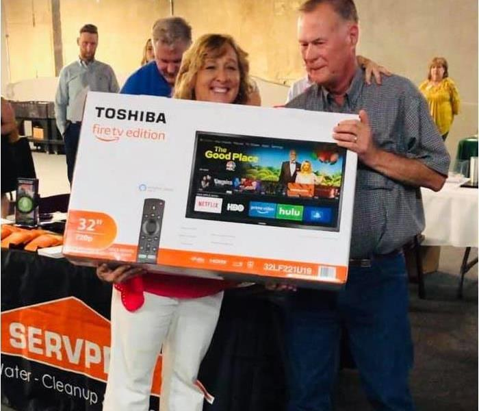 Carolee gives a large screen TV to one lucky winner at an after hours chamber event.